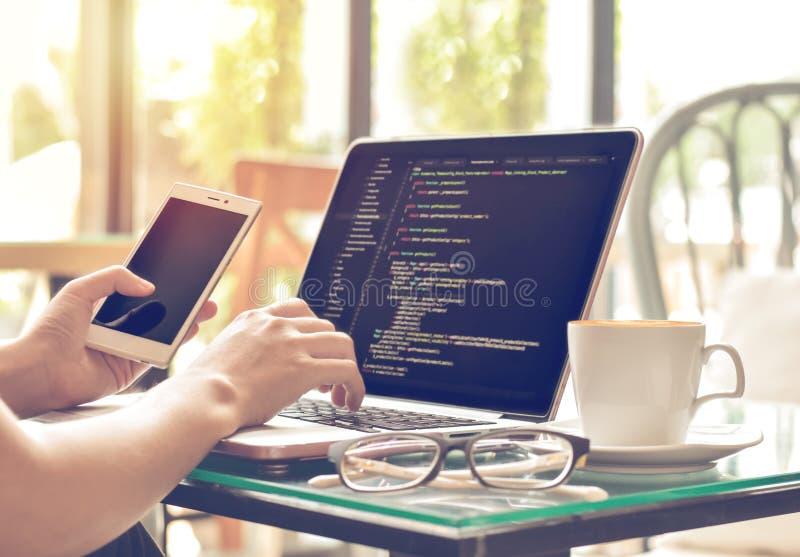Codici sorgente del programmatore femminile e telefono cellulare di battitura a macchina usando in una caffetteria fotografia stock libera da diritti