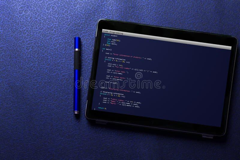 Codificación y programación para el concepto del desarrollo web y del diseño web en la pantalla de la tableta con la pluma azul e imágenes de archivo libres de regalías