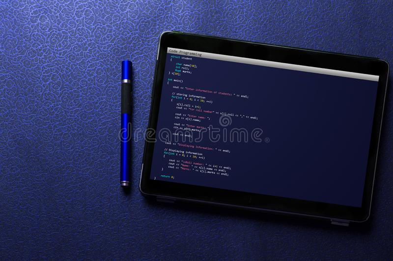 Coding and programming for web development and web design concept on tablet screen with blue pen on blue pattern royalty free stock images