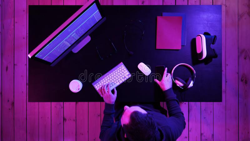 Coding specialist in casual with computer and talking by phone while coding information to create convenient software. royalty free stock photography