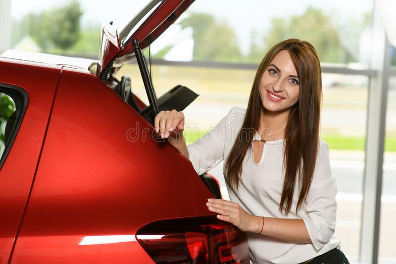 Codo hermoso de la muchacha sus manos en el nuevo coche imagen de archivo