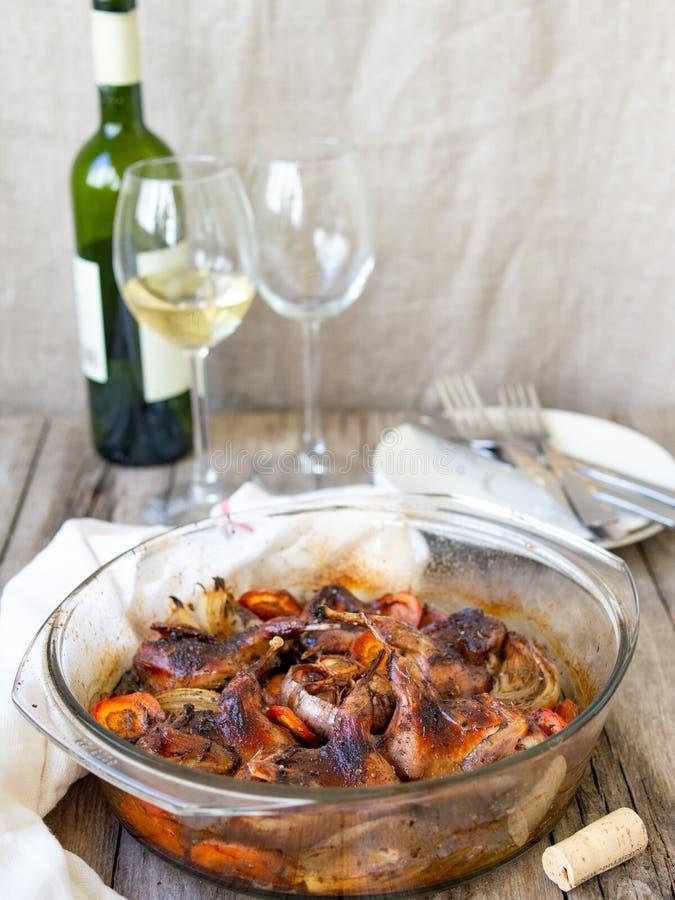 Codornices fritas deliciosas con las verduras - ajo, zanahorias, cebollas, cocidas en una forma de cristal, botella de vino blanc foto de archivo libre de regalías