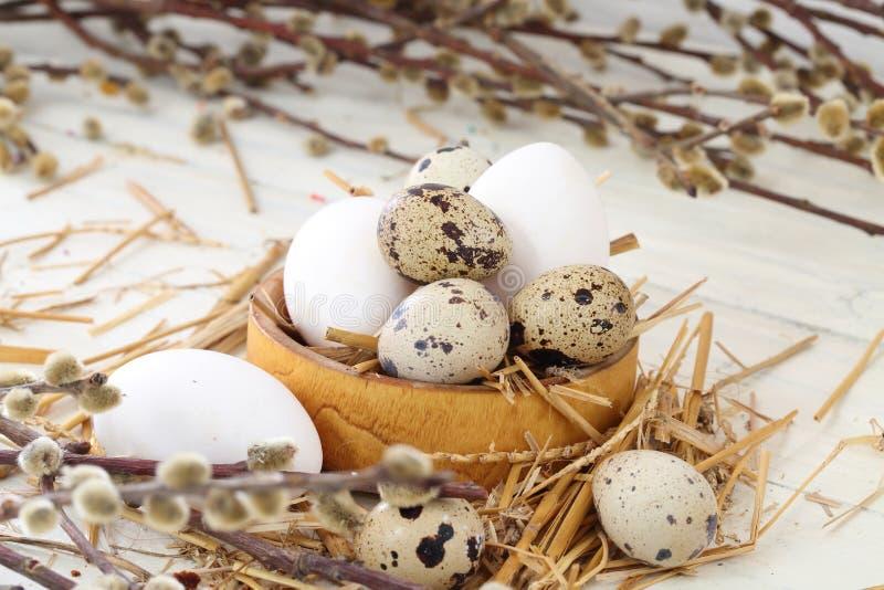 A codorniz e a galinha eggs em ramos de uma bacia de madeira e do salgueiro fotos de stock royalty free