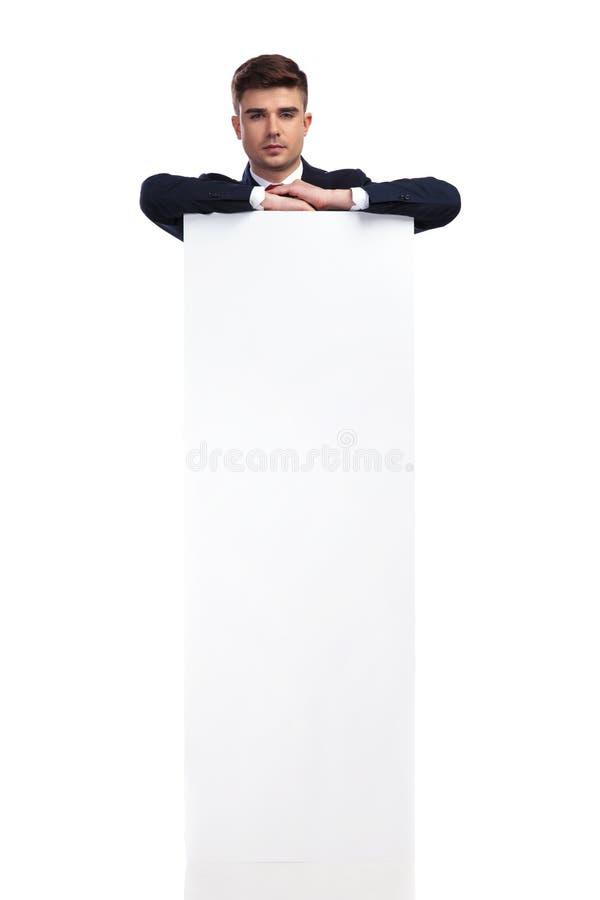 Codos de reclinación del hombre de negocios hermoso en un tablero vacío blanco grande imágenes de archivo libres de regalías
