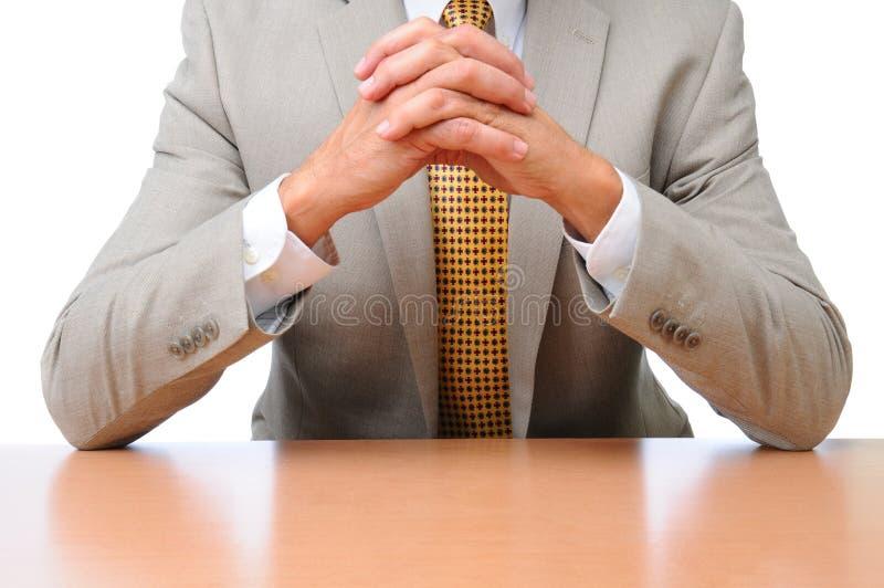 Codos del hombre de negocios en las manos del escritorio plegables fotografía de archivo