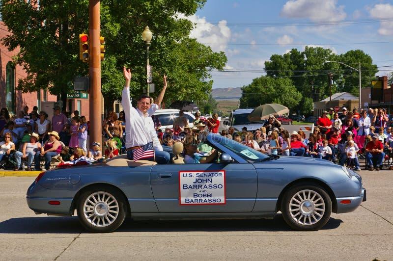 Cody, Wyoming, de V.S. - U S Senator John Barrasso en zijn het berijden van vrouwenbobbi in convertibel en het golven terwijl par royalty-vrije stock afbeeldingen