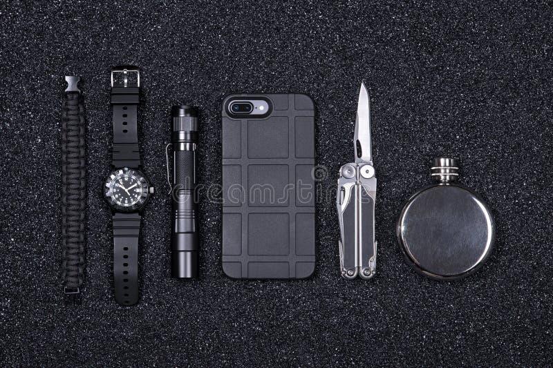Codzienny niesie EDC militarne rzeczy dla mężczyzn wielo- narzędzie, zapalniczka, telefon, taktyczny zegarek, przetrwanie bransol zdjęcia stock