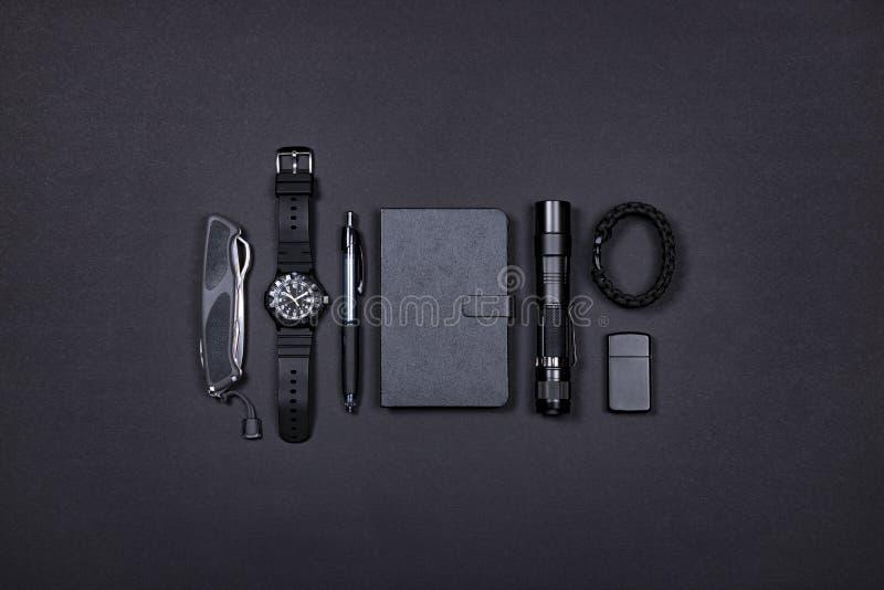 Codzienny niesie EDC rzeczy nóż, zapalniczka, nutowa książka, taktyczny pióro, zegarek, przetrwanie bransoletka i latarka w czarn fotografia royalty free