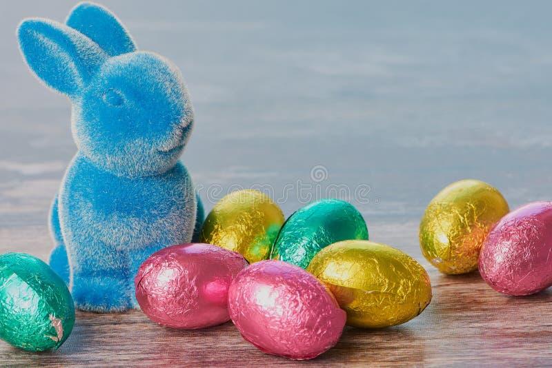 Coelhinho da Páscoa ao lado dos ovos de chocolate no fundo de madeira marrom fotografia de stock royalty free