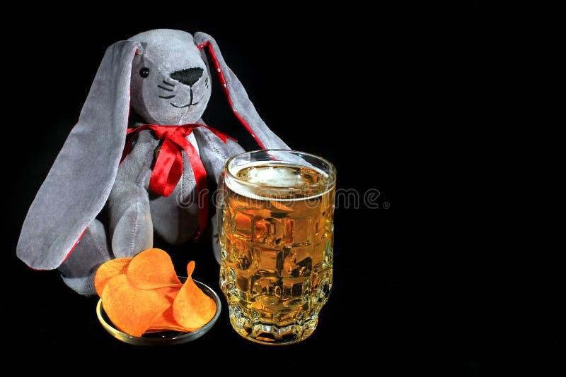 Coelhinho da Páscoa com a caneca de microplaquetas da cerveja e de batata contra o fundo preto foto de stock