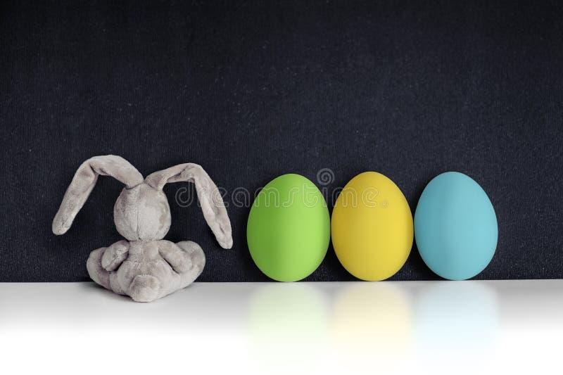 Coelhinho da Páscoa com os ovos coloridos no quadro preto imagens de stock