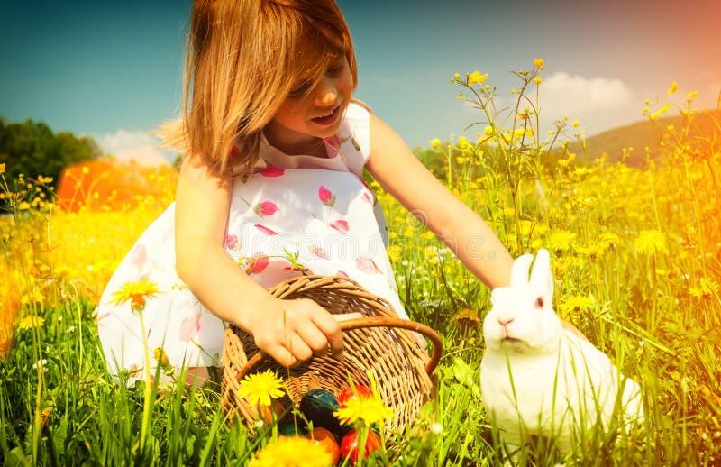 Coelhinho da Páscoa das trocas de carícias da menina no prado com ovos foto de stock