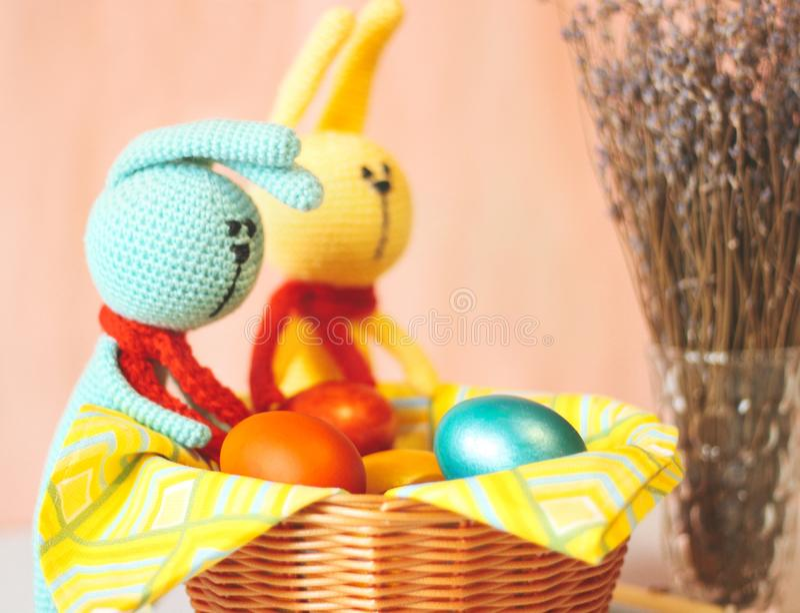 Coelhinho da Páscoa dois perto da cesta com os ovos pintados coloridos imagens de stock royalty free
