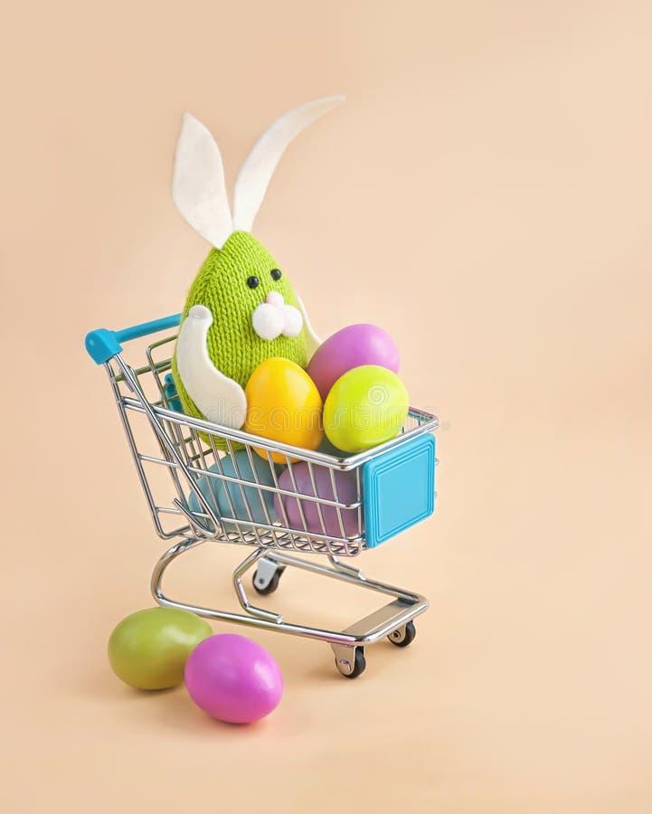 Coelhinho da Páscoa em um trole da compra com ovos coloridos foto de stock