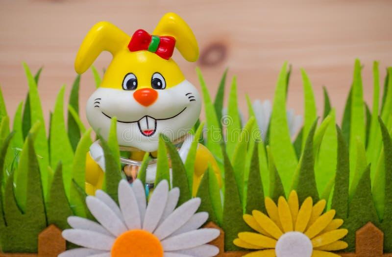 Coelhinho da Páscoa feliz em um ninho com grama e flor foto de stock