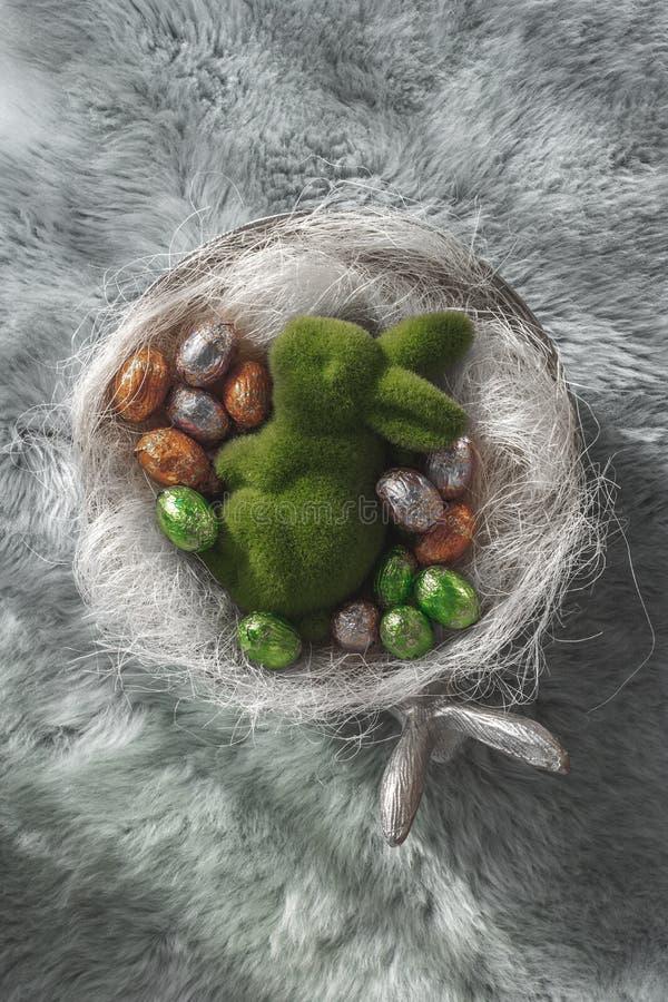Coelhinho da Páscoa que encontra-se em uma bacia com ovo da páscoa do chocolate, fundo da pele fotografia de stock