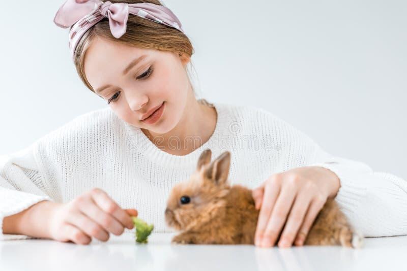 Coelho de alimentação de sorriso da menina com brócolis no branco fotos de stock royalty free