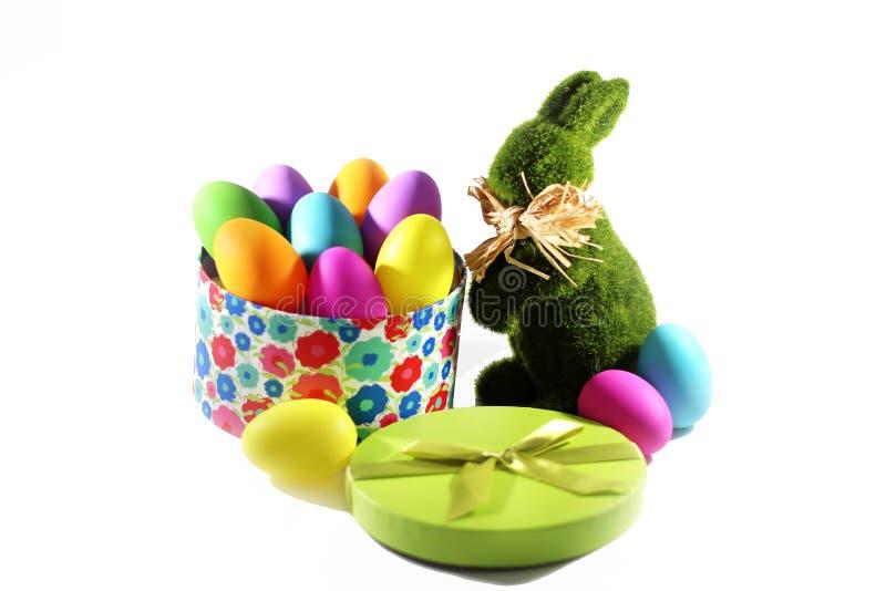 Coelho de coelhinho da Páscoa da grama verde com uma caixa de presente com os ovos coloridos de easter imagem de stock royalty free