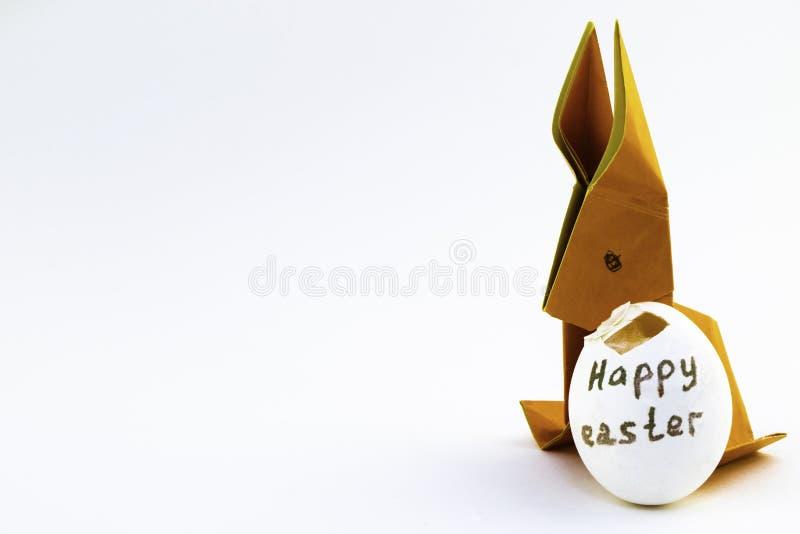 Coelho do origâmi do papel colorido alaranjado Coelhinho da Páscoa e branco com um escudo de ovo desbastado com uma Páscoa feliz  fotos de stock royalty free