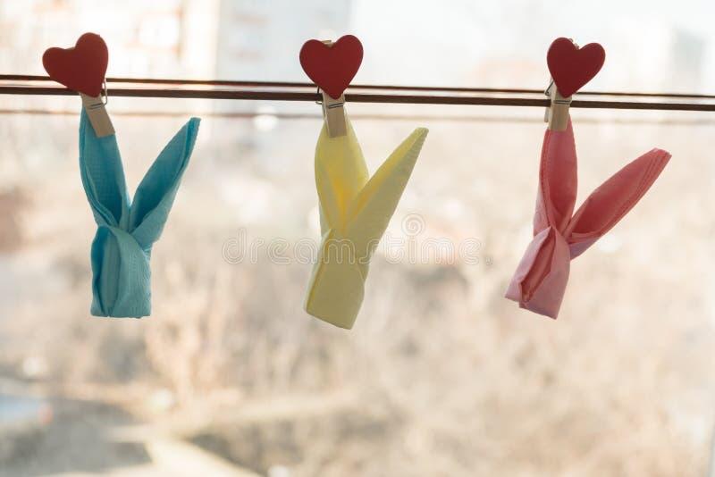 Coelho dos guardanapo nos pregadores de roupa de madeira com os corações que penduram em uma corda imagem de stock
