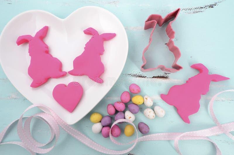 Coelhos cor-de-rosa da cookie do fundente do açúcar dos confeitos da Páscoa fotografia de stock