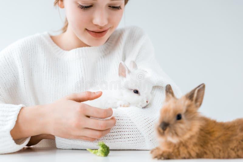 Coelhos de alimentação de sorriso da menina com brócolis no branco foto de stock royalty free