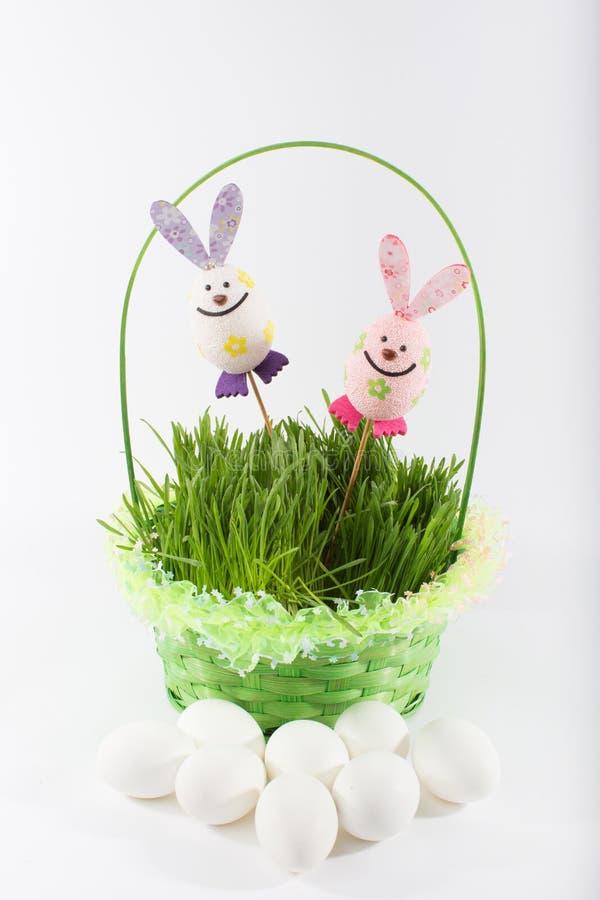 Coelhos de Toy Easter com cesta e os ovos verdes imagens de stock