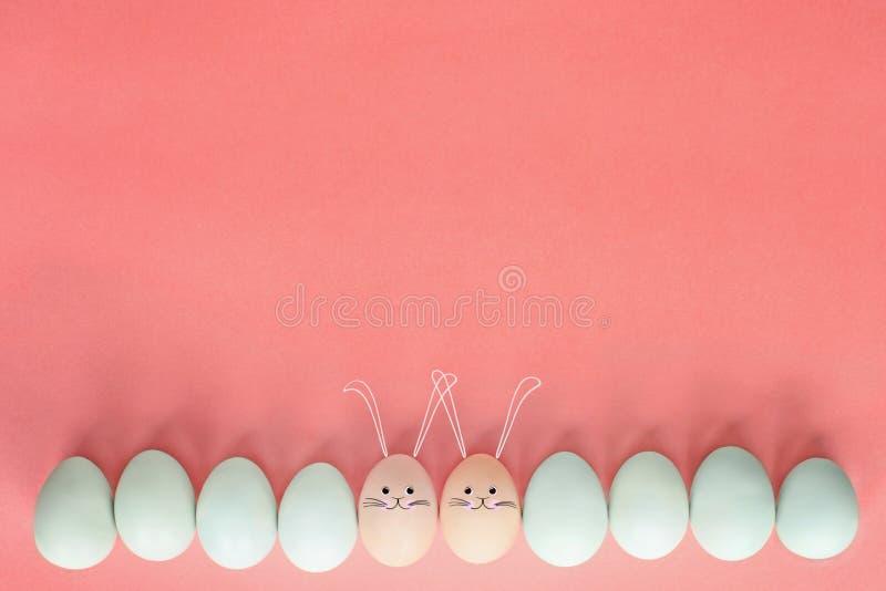 Coelhos do ovo da páscoa sobre o fundo pastel imagem de stock