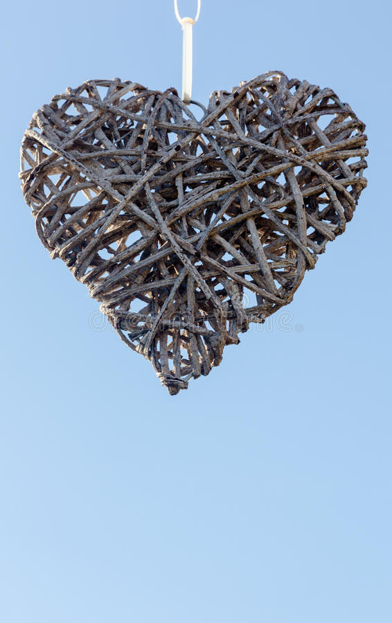 Coeur accroché fait à partir des bâtons en bois tissés sur le backgroun de ciel bleu image stock