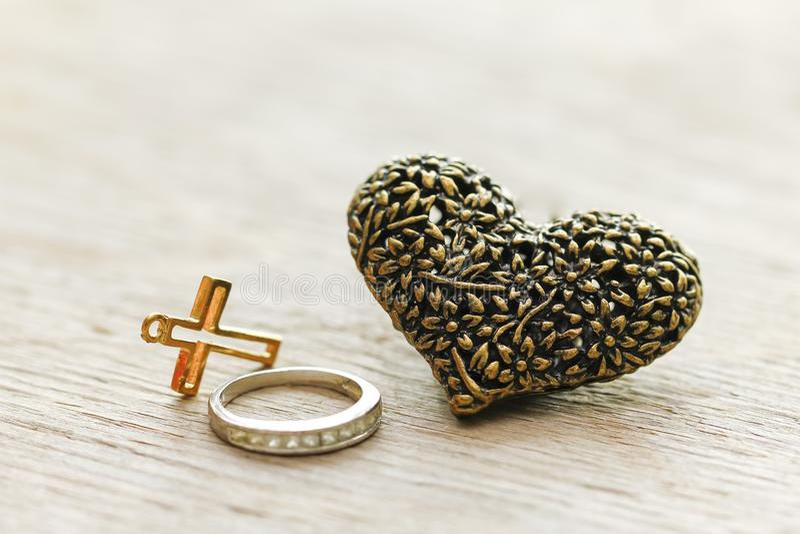 Coeur argenté noir sur le fond en bois avec vieux Christian Cross photographie stock libre de droits