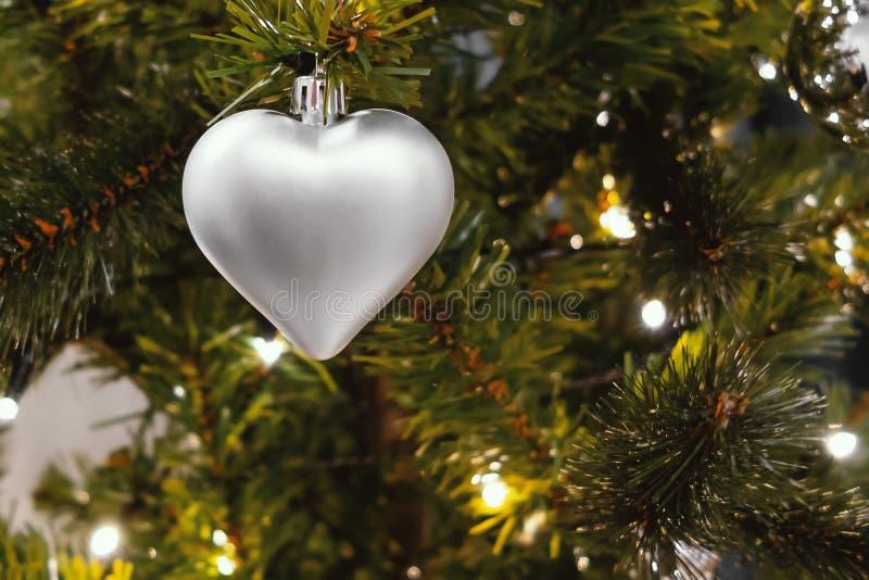Coeur argenté sur le sapin, une partie de l'arbre de Noël avec des décorations de Noël photo stock