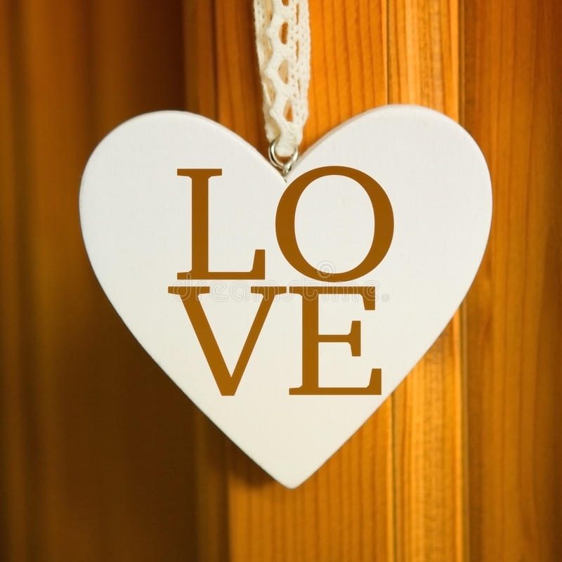 Coeur blanc accrochant sur le bouton de porte avec l'amour de mot photos libres de droits