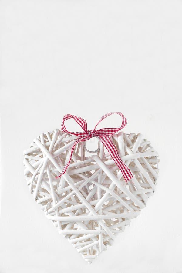 Coeur blanc fait de branches avec un ruban rouge photographie stock