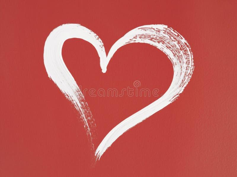 Coeur blanc peint sur le fond rouge photo stock