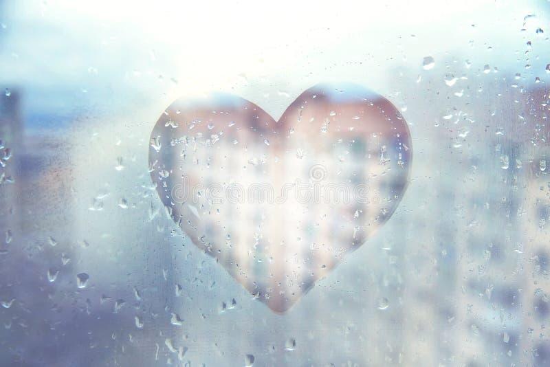 Coeur bleu peint sur la fenêtre humide en verre dans la ville photographie stock