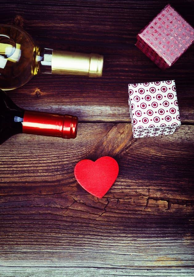 Coeur, cadeaux et bouteilles de vin sur le Tableau photographie stock