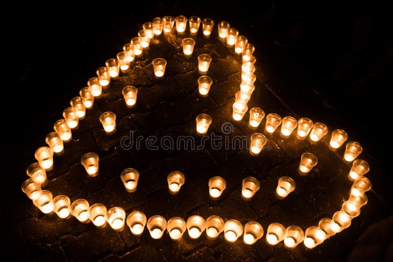 Coeur composé de bougies, au sol, la nuit photos stock