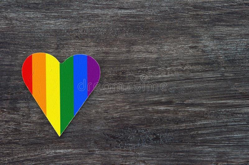 Coeur décoratif avec des rayures d'arc-en-ciel sur le fond en bois gris Drapeau de fierté de LGBT, symbole de lesbien, gai, bisex image libre de droits