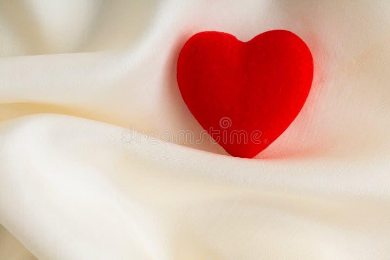 Coeur décoratif en bois rouge sur le fond en soie blanc. photo libre de droits