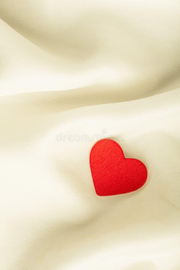Coeur décoratif en bois rouge sur le fond en soie blanc. photo stock