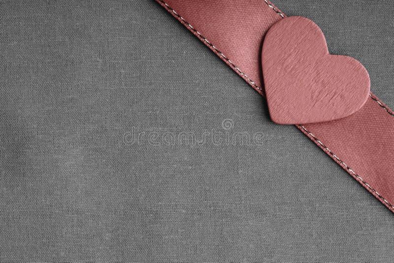 Coeur décoratif en bois rouge sur le fond gris gris de tissu. image stock