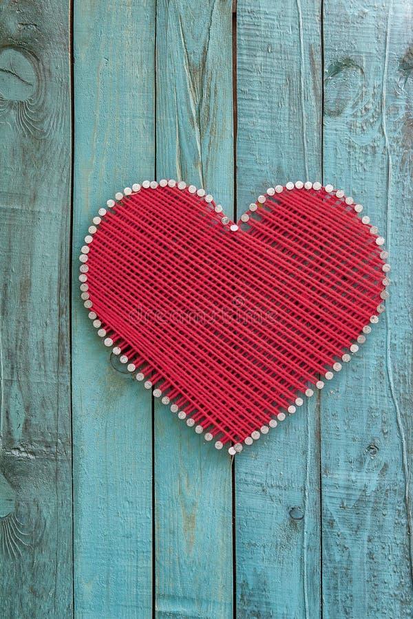 Coeur décoratif fait de fil sur un fond en bois photos stock