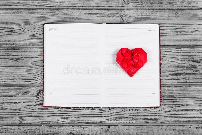 Coeur d'origami de papier rouge Ouvrez le carnet avec des pages propres et un coeur de papier Calibres et milieux image stock