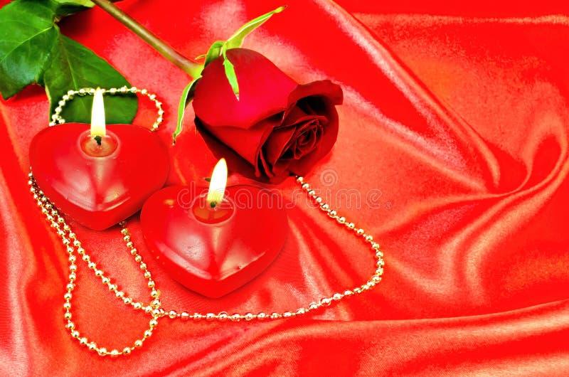 Coeur d'une bougie avec une rose sur une soie rouge images libres de droits