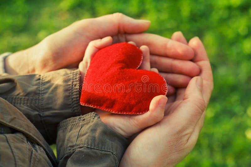 Coeur dans des mains d'enfant et de mère photographie stock