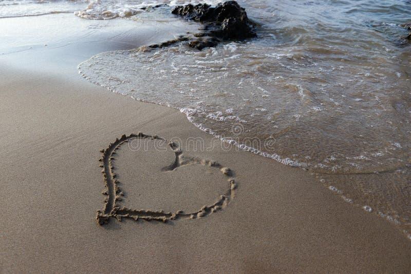 Coeur dans le sable sur la plage image stock