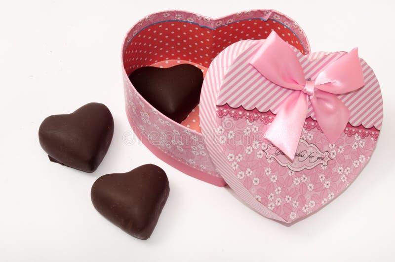 Coeur de chocolat dans le gox en forme de coeur avec l'arc images stock
