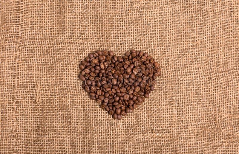 Coeur de graine de café sur le fond brun texturisé de tissu photo libre de droits