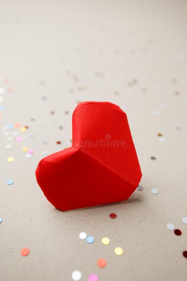 Coeur de jour de valentines d'origami simple et confettis de papier rouges de partie sur le fond gris, fin de jour d'anniversaire images stock