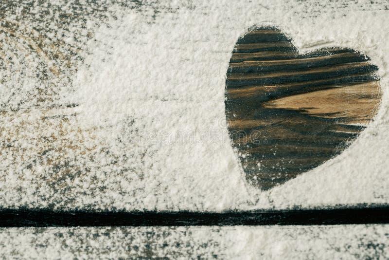 Coeur de la farine blanche sur un conseil en bois Cuisson avec amour Fond de support de vacances Nourriture et cuisine familiale  image stock